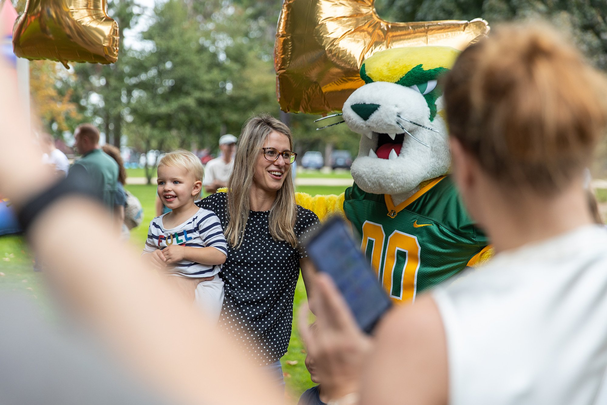 Mother and child with Wildcat Willy at a community event